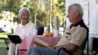 HD Super Slow-Mo: Seniors Having Fun Reading At Campsite video