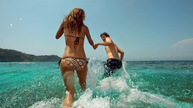 HD Super Slow-Mo: Young Couple Splashing Into The Sea video