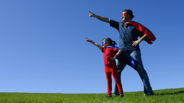 Superhero father shows his daughter how to be  a superhero against blue sky video