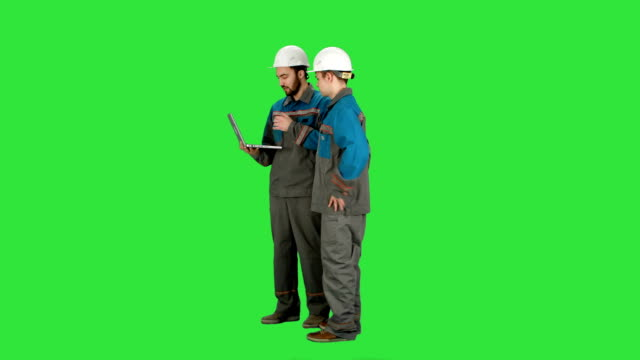 Supervisors using laptop at construction site on a Green Screen, Chroma Key video