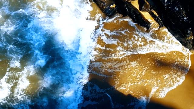 Surf breaking on golden beach video