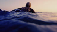 Surf girl paddles by camera on a California summer evening on surfboard shot in slow motion at sunset. video