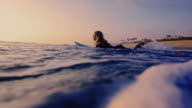 Surf girl runs out into the California ocean on surfboard shot in slow motion at sunset. video