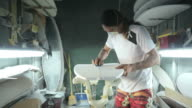 Surfboard making, Shaper is shaving and cleaning a line on a surfboard video