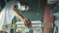 Surfboard making, Shaper measuring blank surfboard with a level ruler video