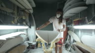 Surfboard shaping, shaper examining and placing the blank surfboard on the work station video