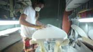 Surfboard shaping, Shaper using a foam sander to shape the bottom of the surfboard video