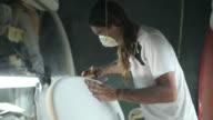 Surfboard shaping, Shaper using a foam sander to shape the side of the surfboard video