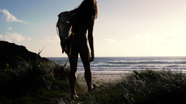 Surfer girl walking to beach with surfboard at sunrise. Slow motion. video