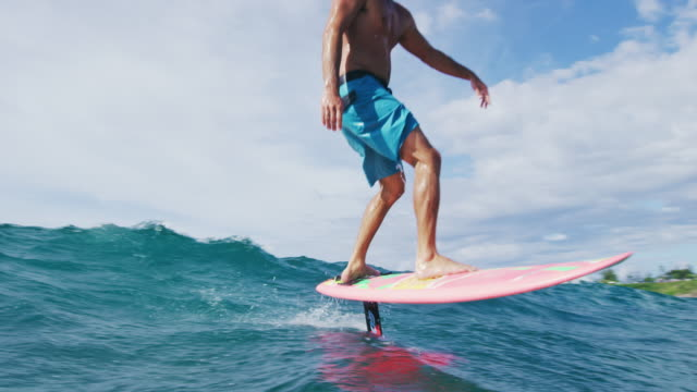 Surfer on hydrofoil surfboard riding blue ocean wave. video