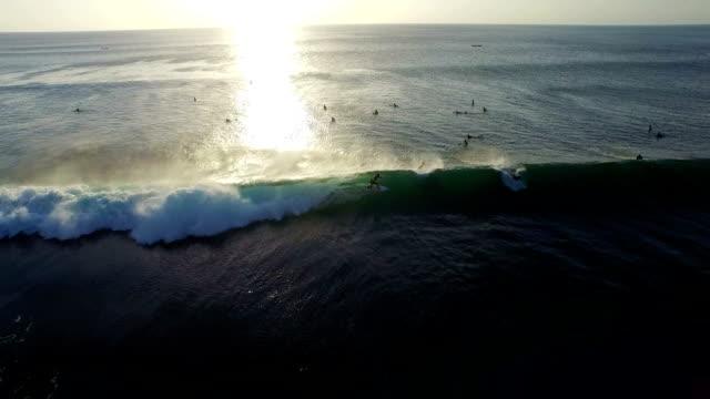 Surfer riding a wave in setting sun (Balangan beach, Bali, Indonesia) video