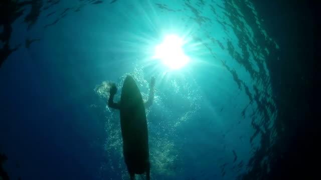 SLOW MOTION UNDERWATER: Surfer sportsgirl paddling on a surf in open water ocean video