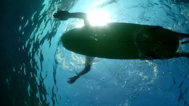 SLOW MOTION UNDERWATER: Surfer sportsman paddling on a surf in open water ocean video