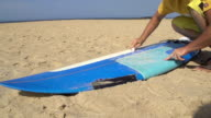 Surfer waxing his surfboard video