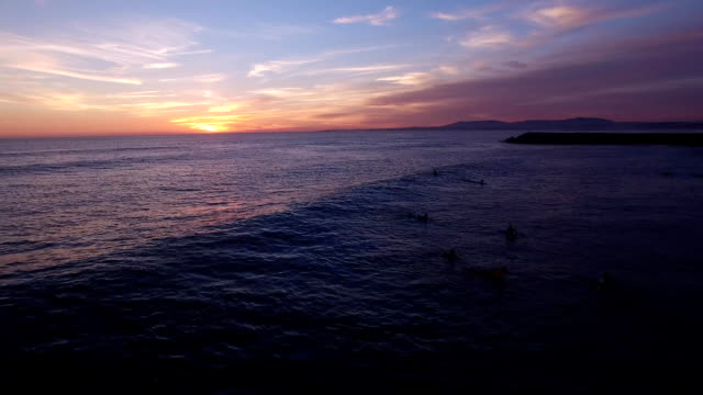 Surfers in the water during a beautiful sunset aerial view video