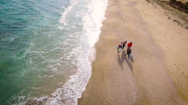 Surfers walking down the beach 4K video