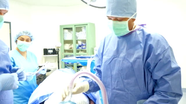 Surgeon and nurses wait as anesthesiologist administers anesthesia video