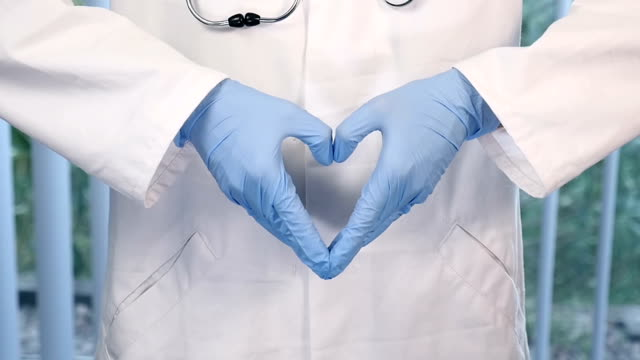 Surgeon making heart shape with hands video