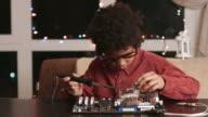 Surprised black boy fixing motherboard. video