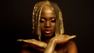 Surreal Fashion Portrait of African American Female Model with Golden Glossy Headwear. Creativity concept, black studio background video