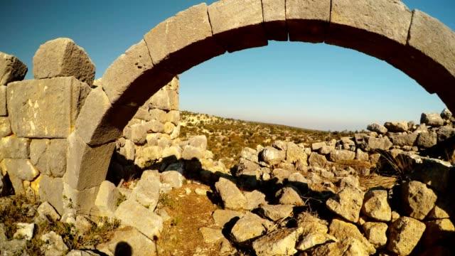 Surviving arch among ruins on background blue sky Adamkayalar Mersin province Turkey video