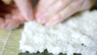Sushi chef preparing rice for sushi roll in studio video