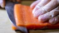 Sushi chef slicing fresh salman steak in studio video