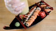 Sushi master pouring sushi rolls with unagi sauce video