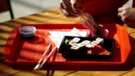 Sushi sets. Human hand dips a sushi by chopsticks in a soy sauce cup video