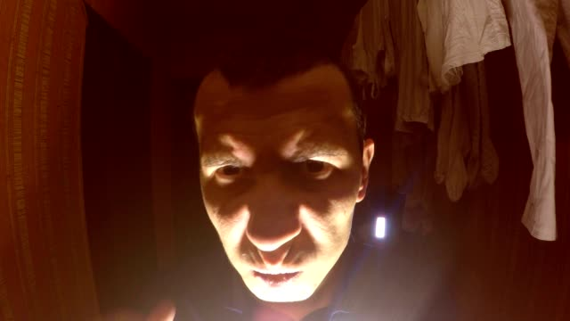 suspicious  man maniac in the room below the hall light night video