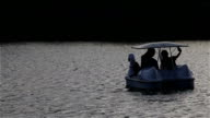 Swan shaped pedal boats floating on a central pond in the park video