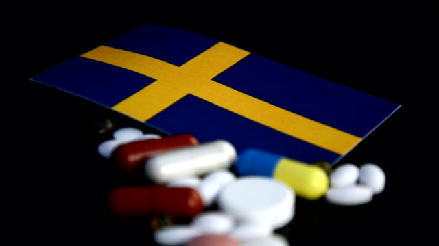 Swedish flag with lot of medical pills isolated on black background video