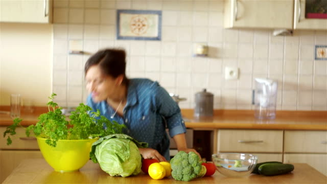 A sweet brunette is cutting vegetables in the kitchen. She sniffs the green of parsley and eats a piece with pleasure. video