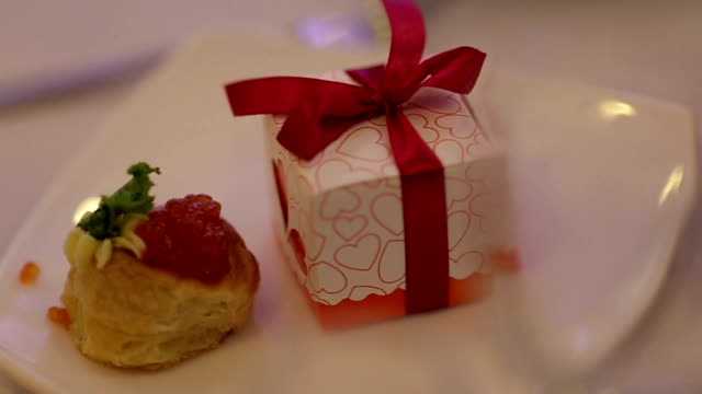 Sweet cake and present in the box with red ribbons on the plate video