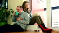 sweet couple relaxing on warm radiator at home. video