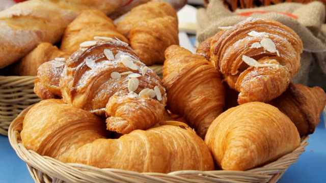 Sweet croissants in a basket on the table. Breakfast background with almond croissants. Delicious fresh croissants, close-up video