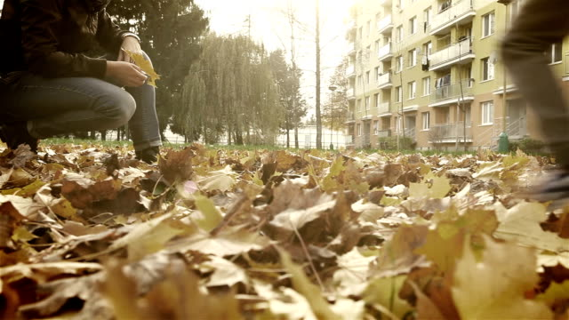 Sweet family scene: son brings a beautiful bouquet of autumnal leaves to his mother video