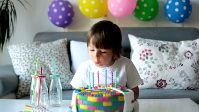 Sweet little child, boy, celebrating his sixth birthday, cake, balloons, candles, cookies. Childhood happiness concept video