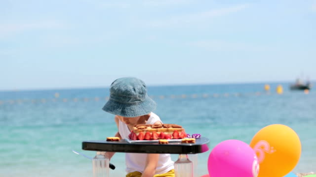 Sweet little child, boy, celebrating his sixth birthday on the beach, cake, balloons, candles, cookies. Childhood happiness concept video