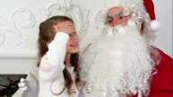 Sweet little girl on Santa Claus lap telling him what she wants for Christmas video