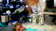 sweet sleep, little cute girl sleep, near the fireplace where the fire burns, hugging a doll, The child sleeps near a Christmas tree, waiting for Santa Claus video