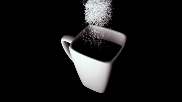 Sweetener is poured into a cup on a black background, slow mo video