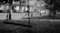 Swinging swing, passing car in background, black and white video