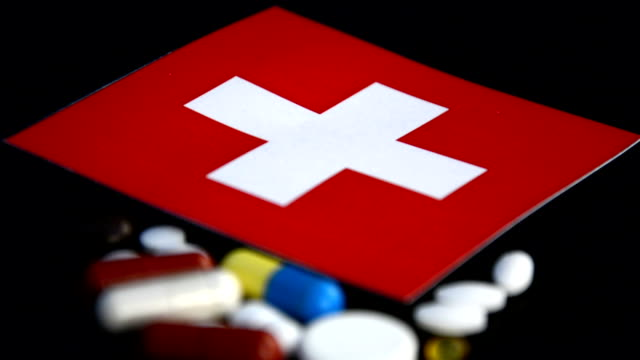 Swiss flag with lot of medical pills isolated on black background video