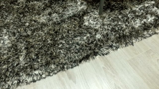 Synthetic carpet on the laminate in the home interior. Close-up video