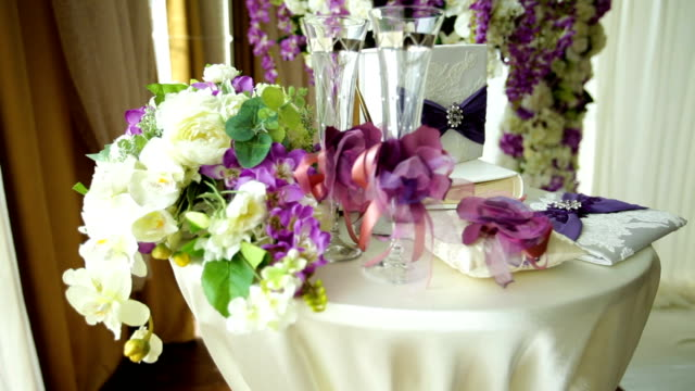 Table for a wedding ceremony with glasses of champagne, rings and a bouquet of flowers video