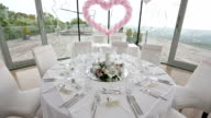Table setted fof guests. Luxury wedding hall decorated with pink balloons and flowers video
