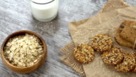 Table top of cookies, oatmeal, and a glass of milk on a rustic wooden table video
