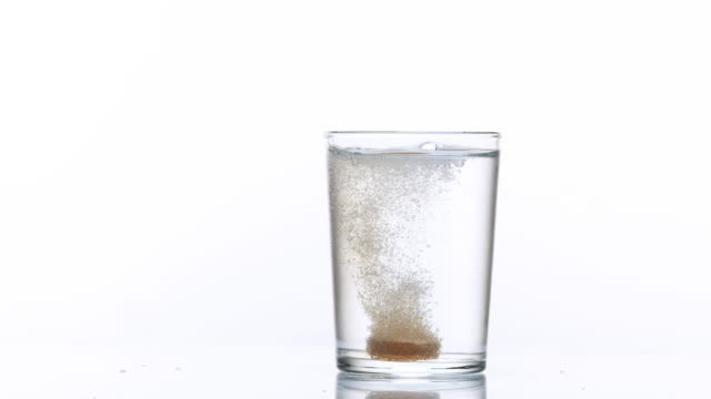 Tablet or Vitamin Falling and Dissolving into a Glass of Water against White Background, Slow Motion 4K video