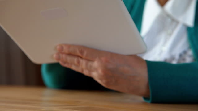 Tablet PC in a mature woman hands - close up video
